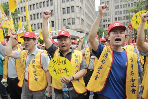 "Taiwanese workers shout slogans ""Strive for Working Right, Want Indemnifier"" during a May Day rally in Taipei, Taiwan, Sunday, May 1, 2016. Thousands of protesters from different labor groups protest on the street to ask for raising minimum wage and shorter working hours. (AP Photo/Chiang Ying-ying)"